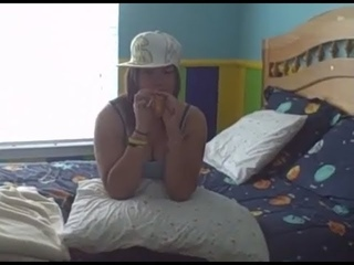 Chick blows up a yellow balloon on the bed and pops it