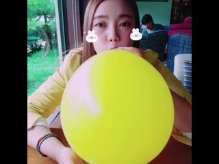 Cute asian yellow balloon blowing