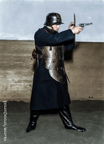 Польский полицейский в полной штурмовой экипировке стальной кирасе и штальхельме, с 7,62-мм револьвером системы Нагана и малым противопульным щитом Варшава, 1934 год. Колонизация.© Willem van de