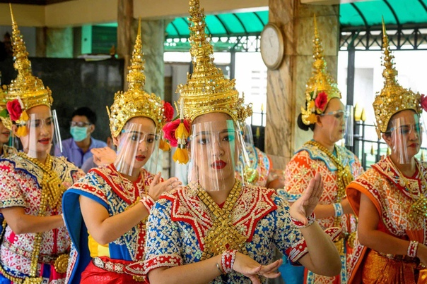 Тайские танцовщицы в защитных щитках выступают в храме Эраван после смягчения карантина в стране.